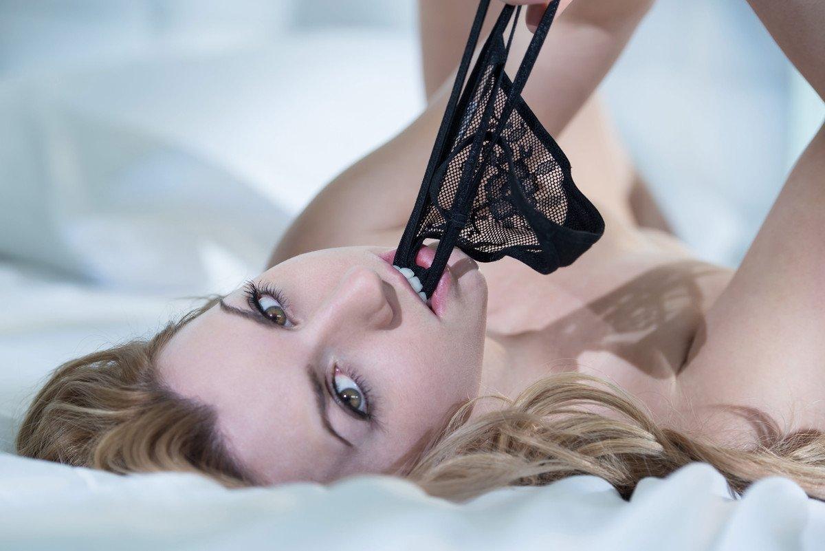 Модель лежа на кровати от возбуждения грызет свои стринги